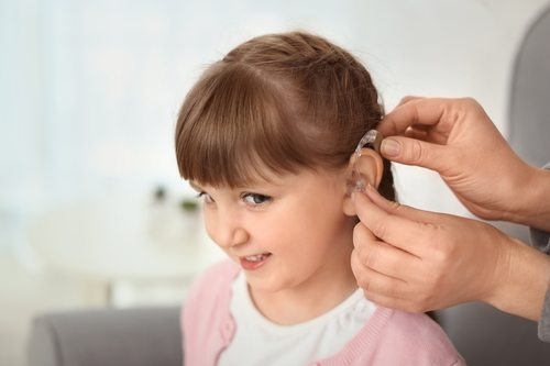 child with hearing loss being fitted for hearing aid
